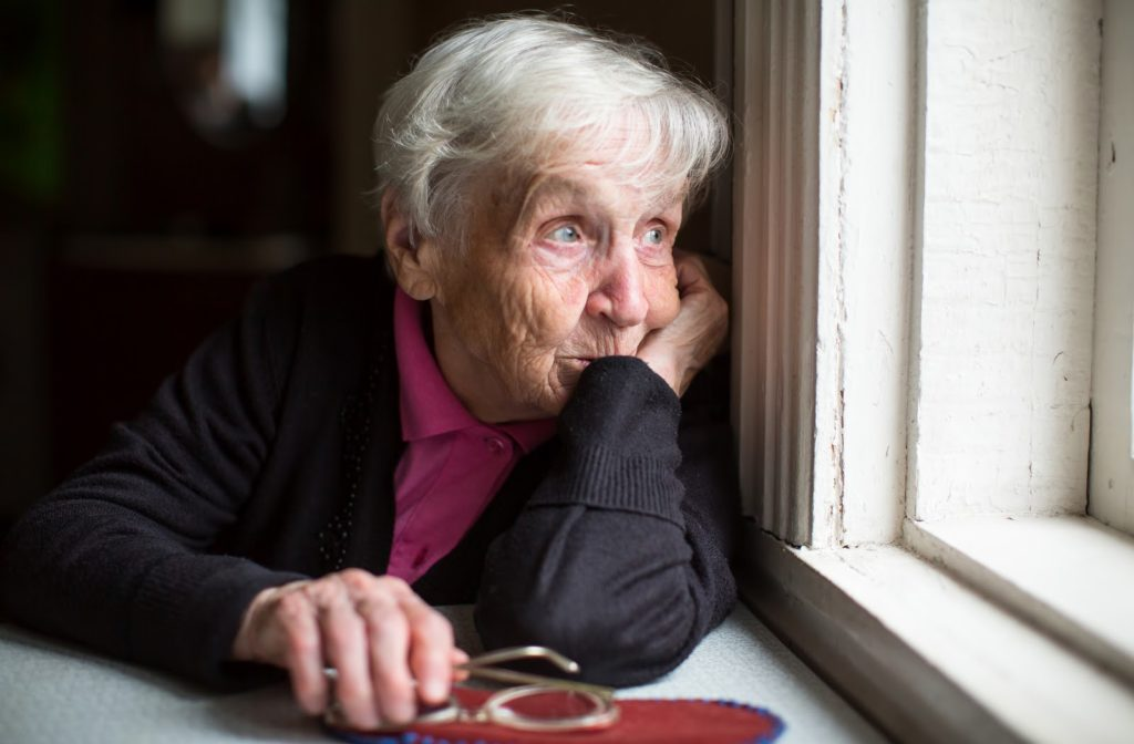 Sad senior women looks out window as she leans against it